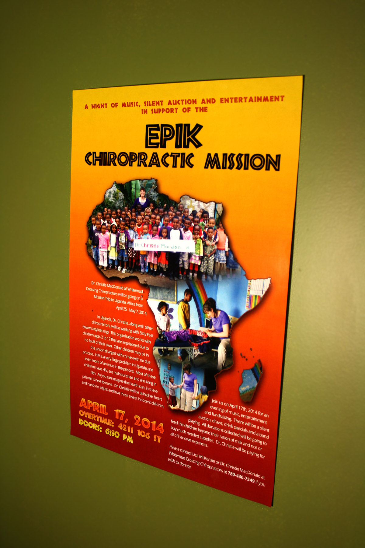 A poster hung on a wall designed to promote Dr. Christie MacDonald's trip to Uganda, Africa.
